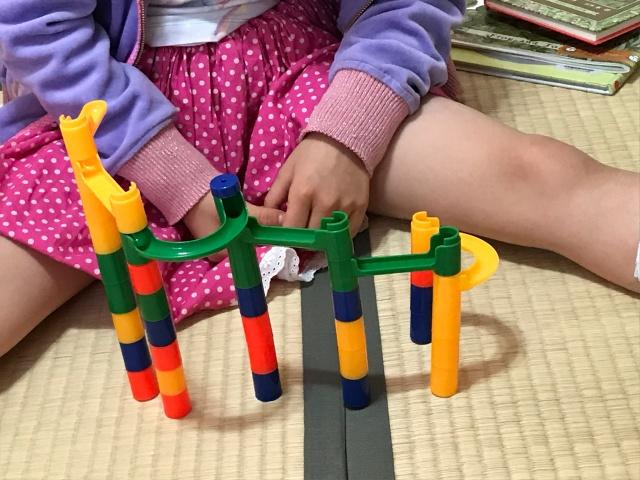 100均のビー玉転がしを組み立てている子供。どんどん隣のスロープに流れる形