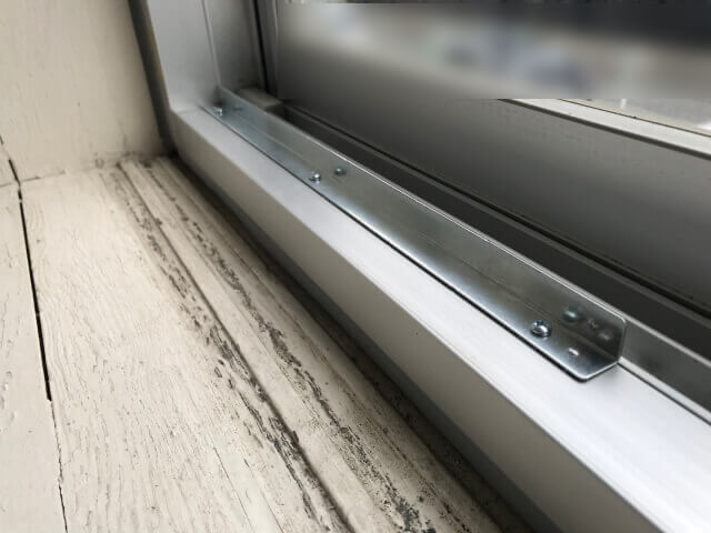 コロナ窓用エアコン、窓サッシに立ち上がりが無いので、補助器具の部分に穴をあけネジで固定した